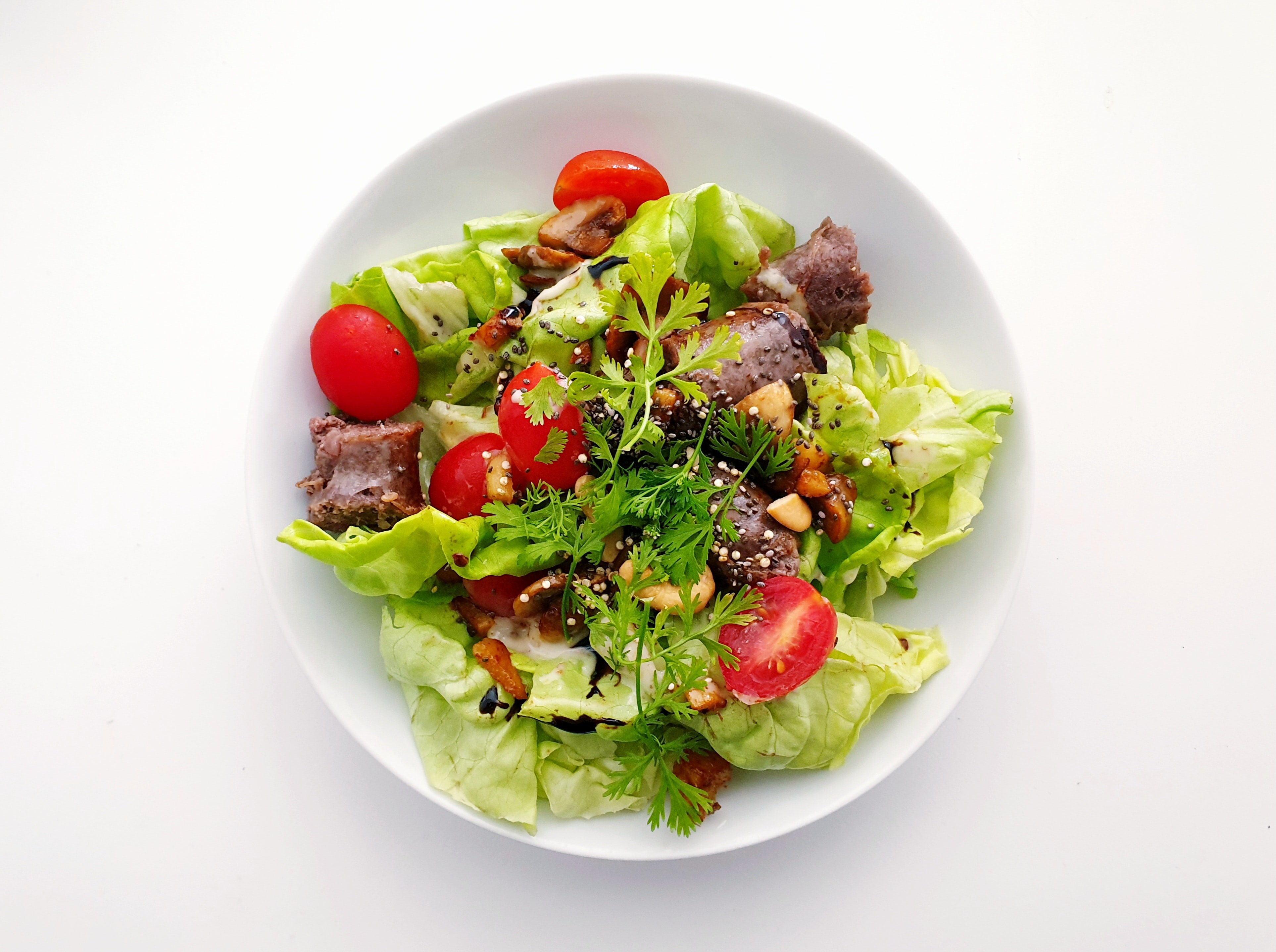 Lettuce with tomatoes, fresh herbs, and mushrooms.