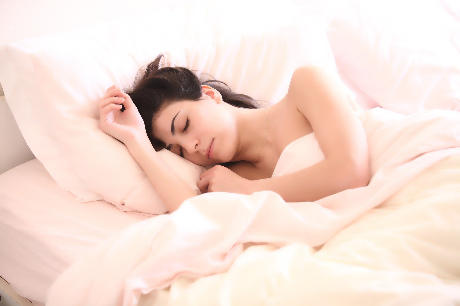 Young woman lying in bed, sleeping.