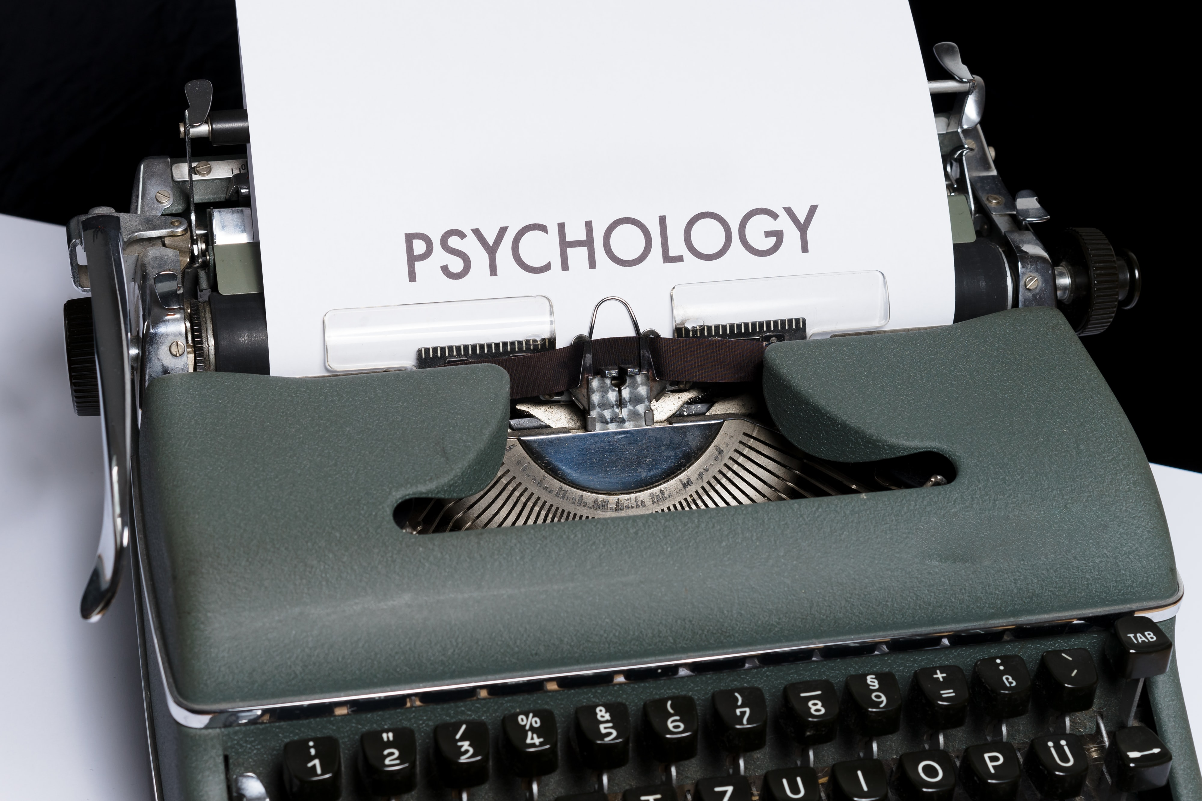 An old-style typewriter with a sheet of paper with the word PSYCHOLOGY.