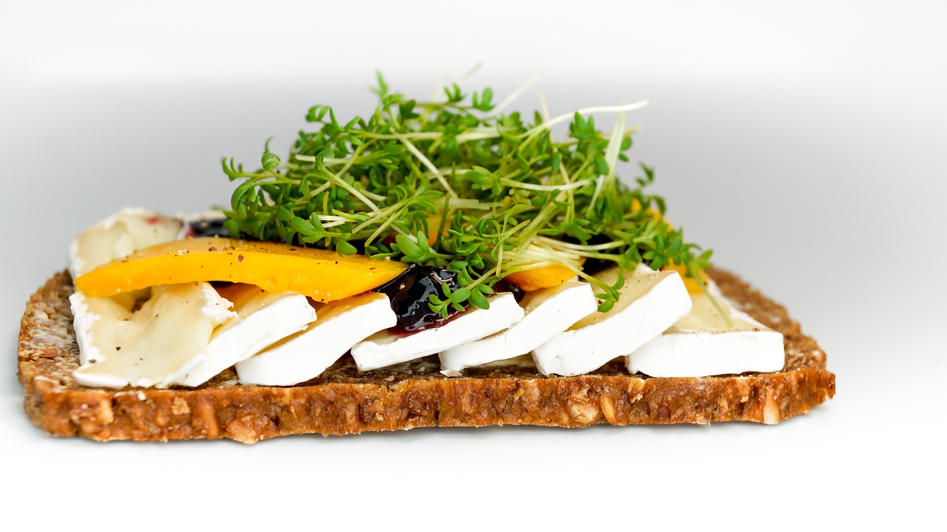 Whole grain bread with cheese and watercress.