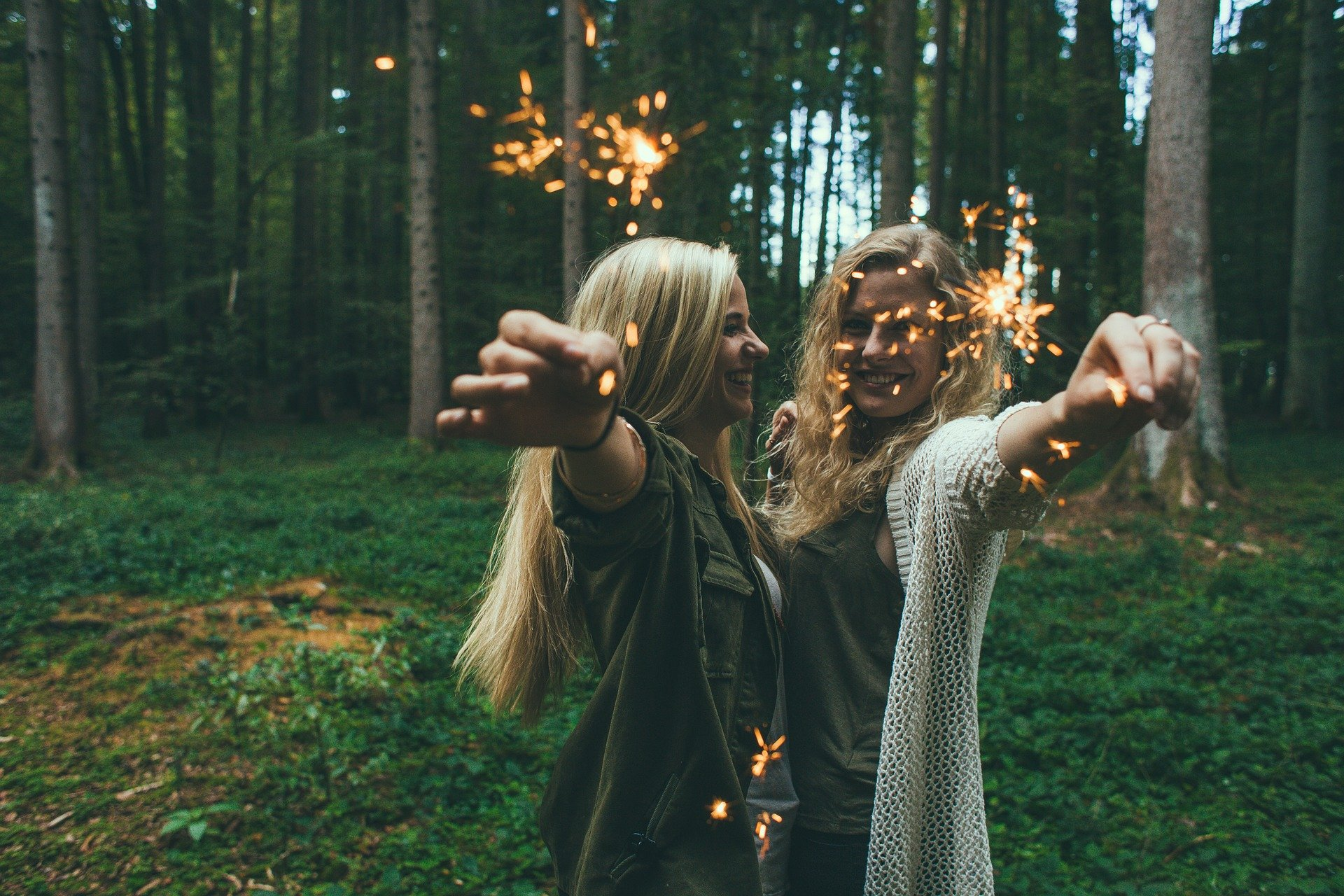 Two women in the forest, holding sparklers in their hands.