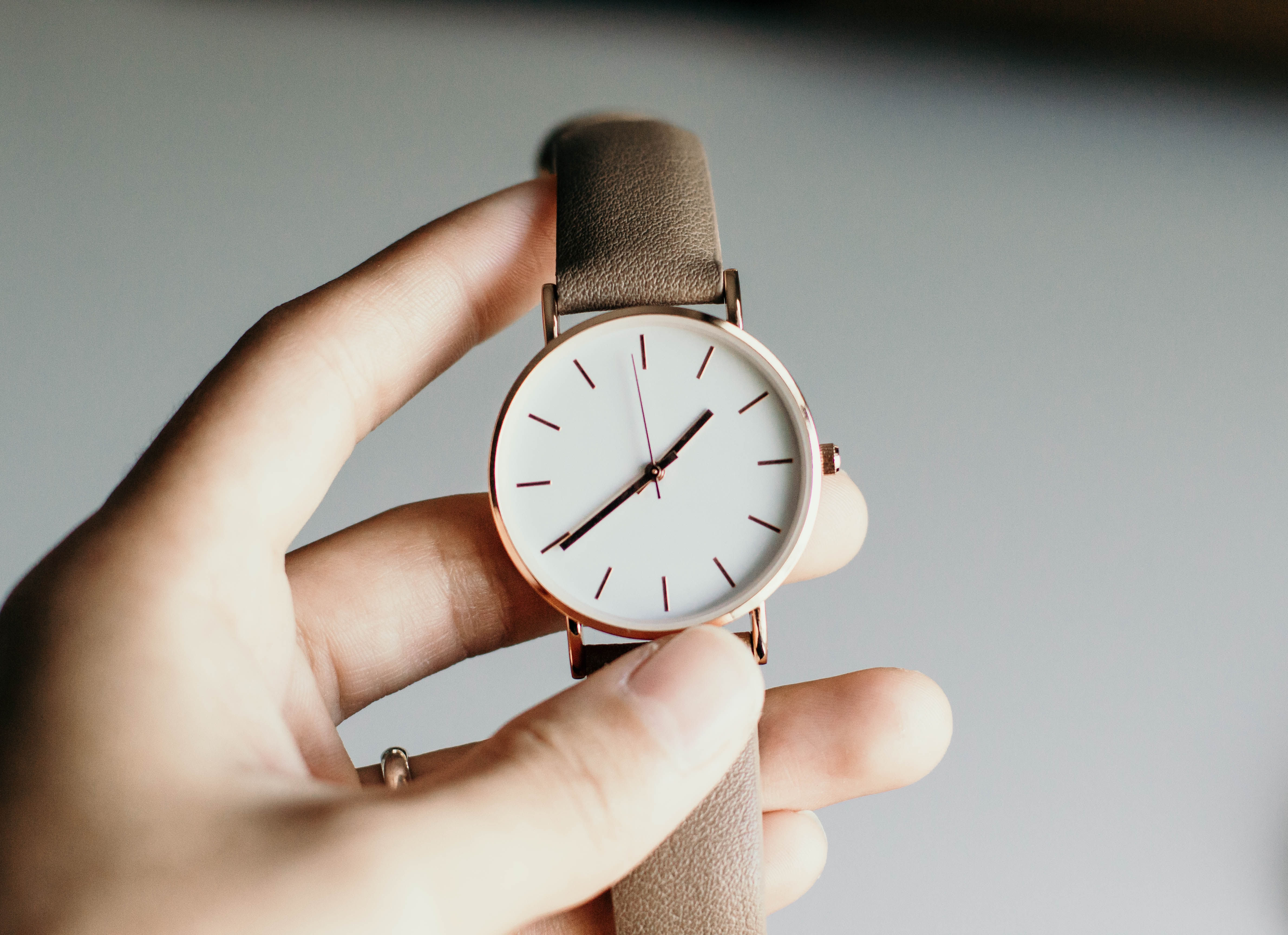 Person holding a watch in her hand.
