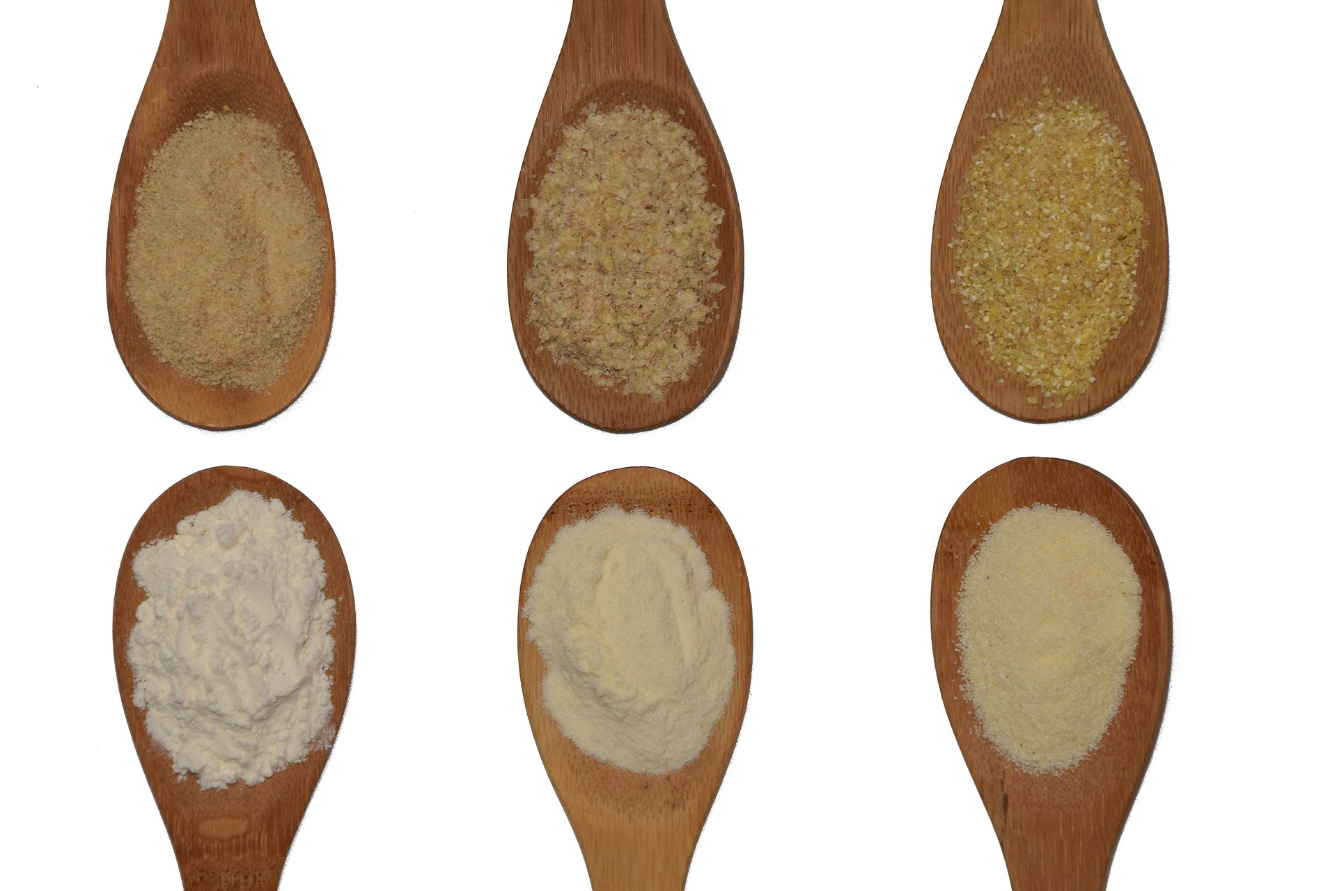 6 wooden spoons with different types of grains.