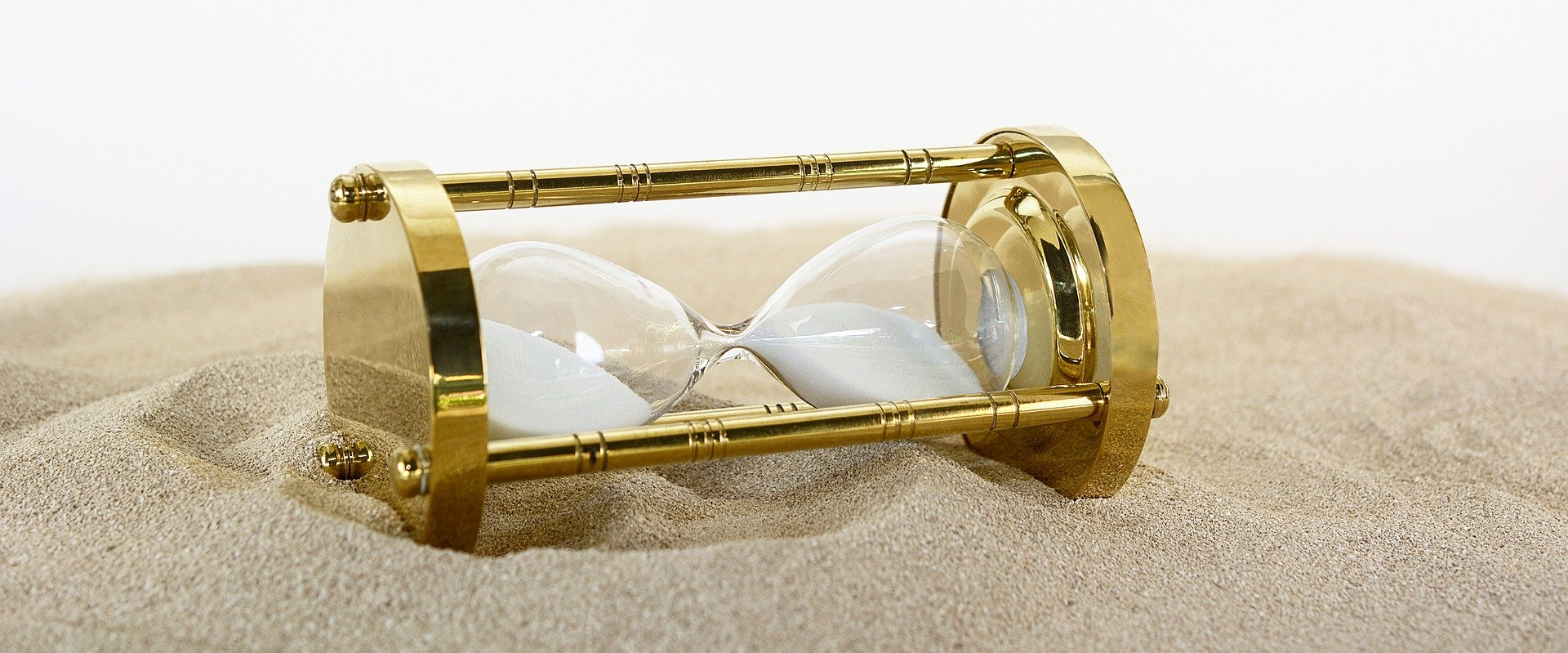 A golden hourglass lying in sand.