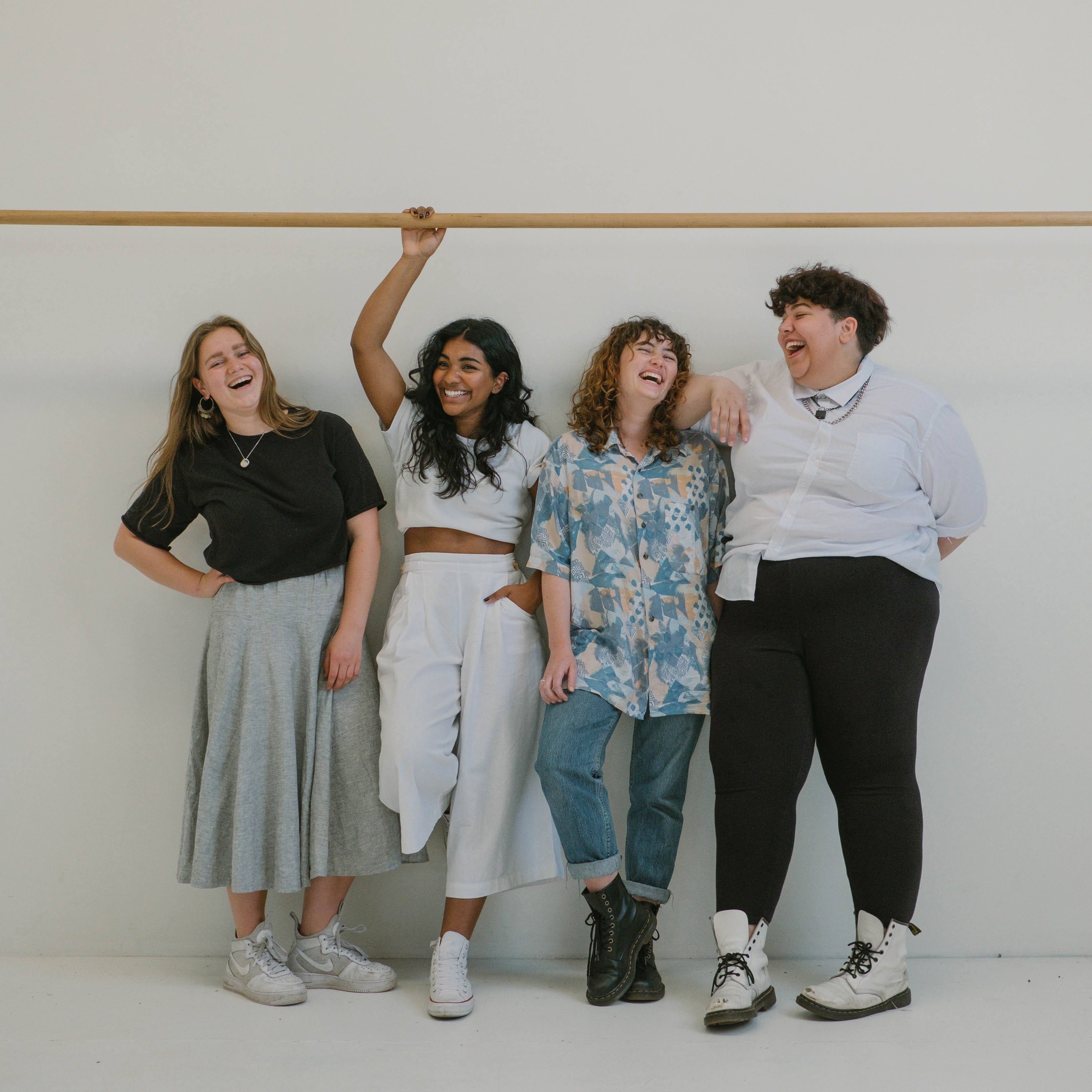 Four women standing next to each other, most of them are overweight.