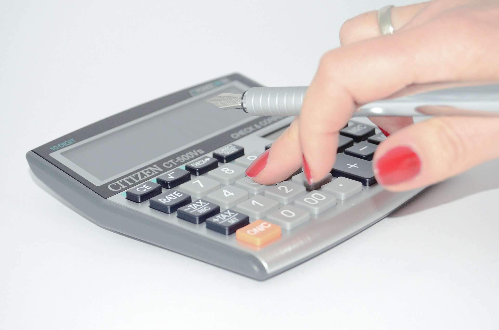Woman with red fingernails typing on a calculator.