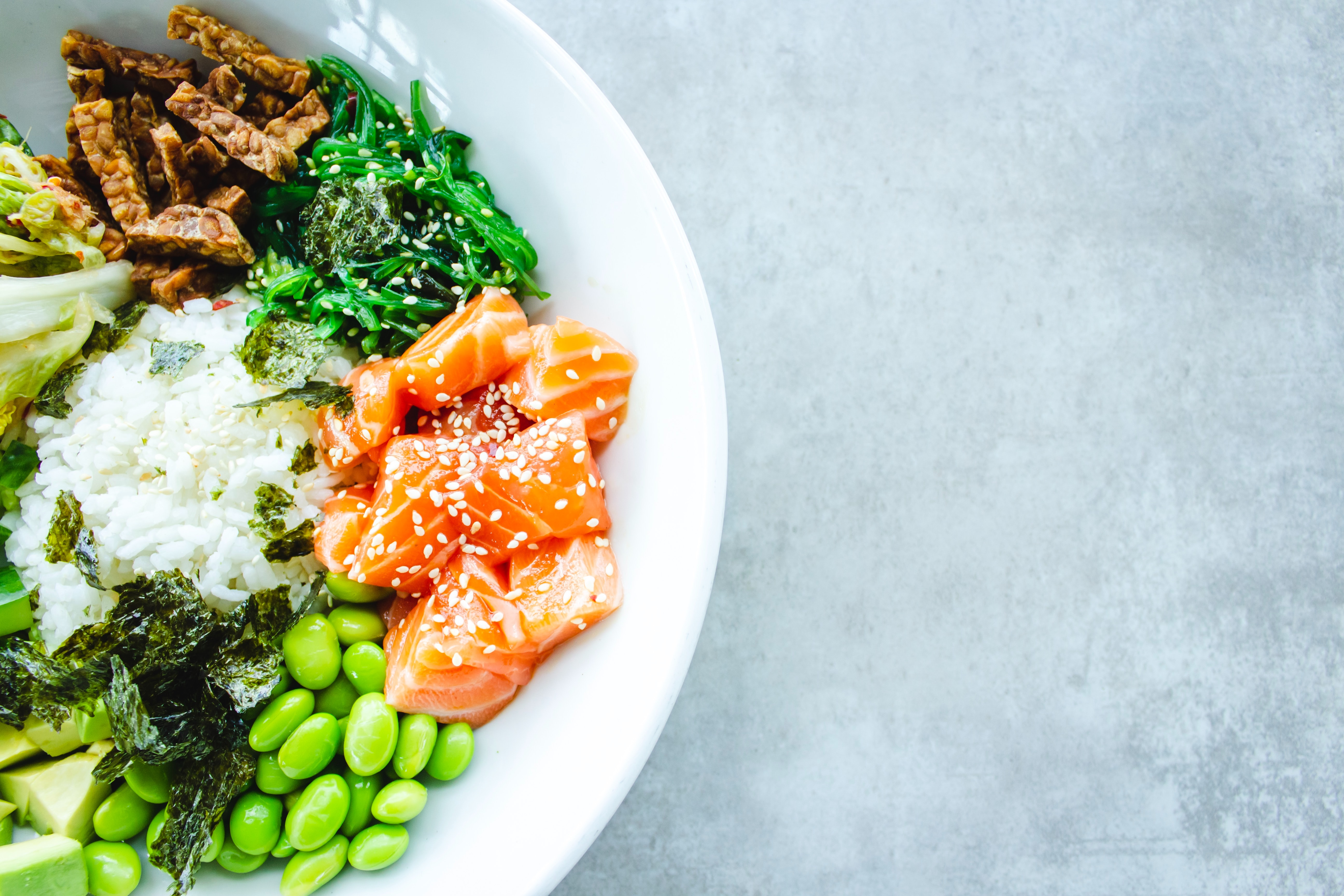 Plate with salmon, different green vegetables and some rice.