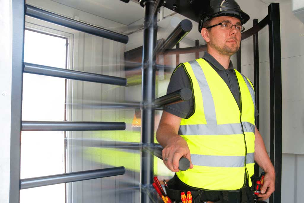 Worker walks through a turnstile access point on a worksite