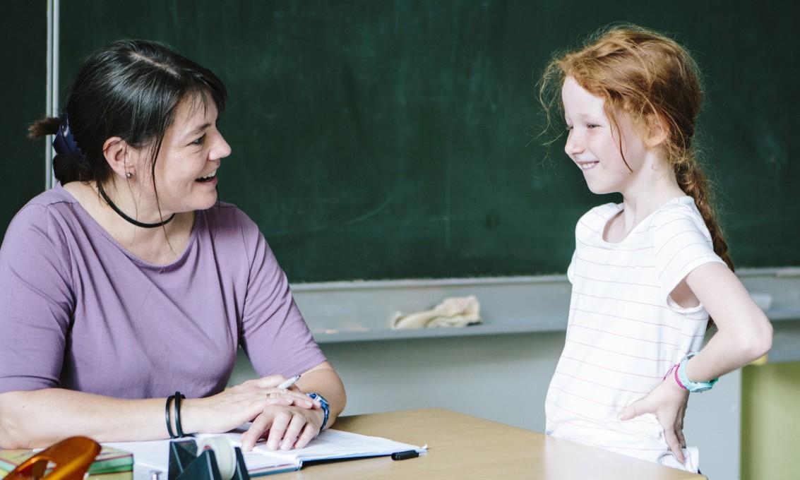 Smilende klasseforstander og elev som holder en samtale