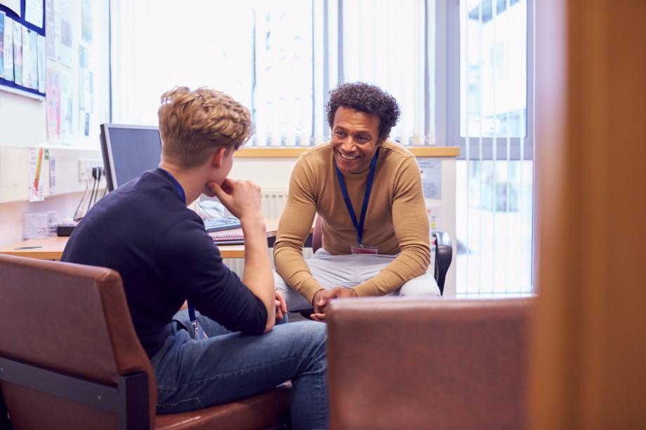 En laerer og elev som har en hyggelig samtale sammen på kontoret til laereren