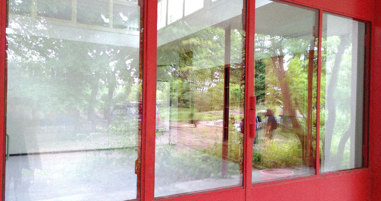 A Reflection of people and trees on a Glassdoor.