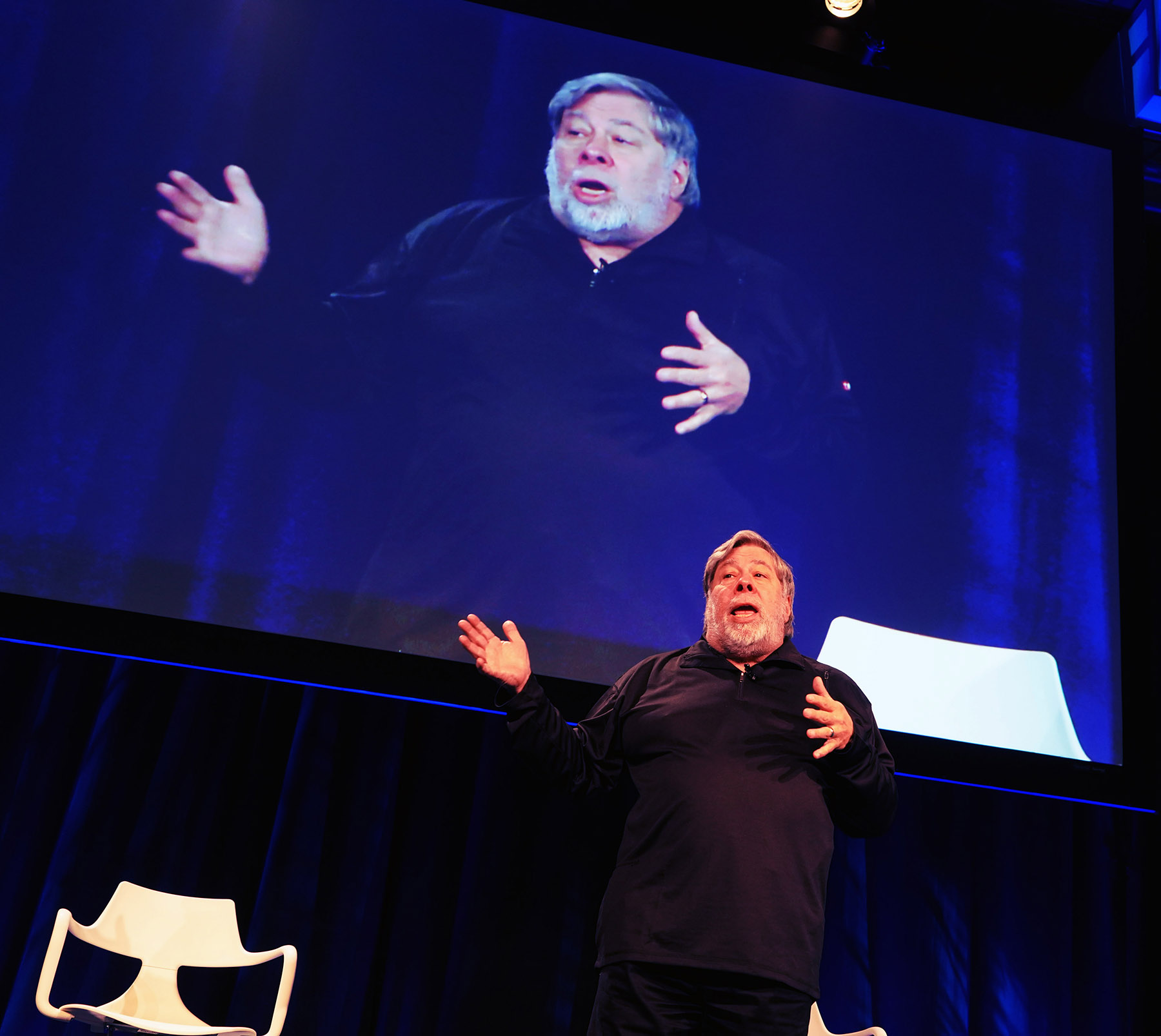 man on stage at CRE.Converge conference using his hands to gesture broadly