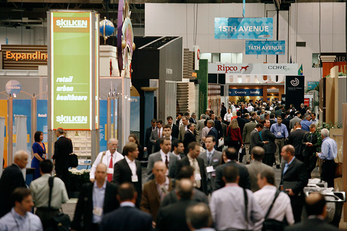 crowd of people in business suits walk past sponsored booths at RECon in Las Vegas, NV