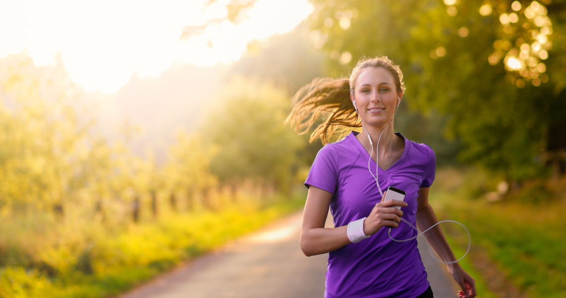 Young woman with headphones listening to YouTube playlist while running