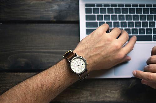 Una persona mira su reloj con un teclado de ordenador de fondo