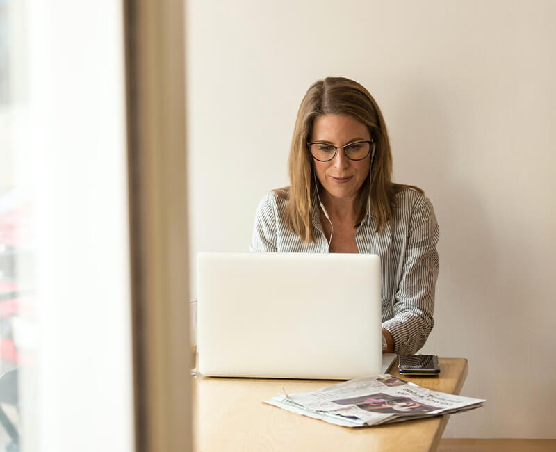 Woman on laptop with earphone on