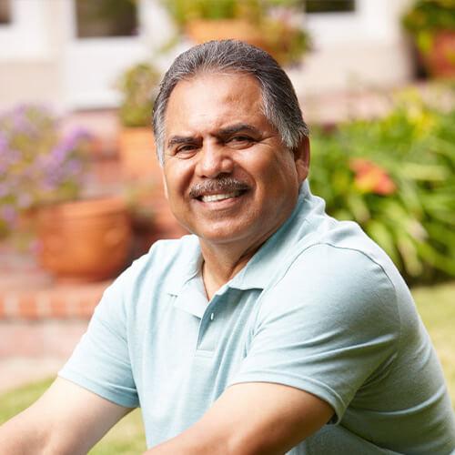 Middle-aged hispanic man smiling in garden