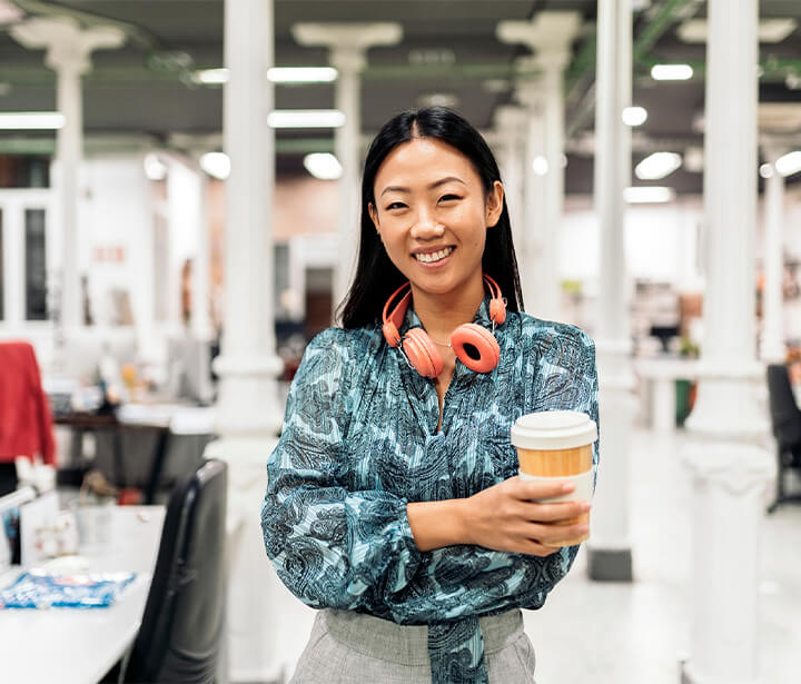 Smiling woman holding coffee cup in office