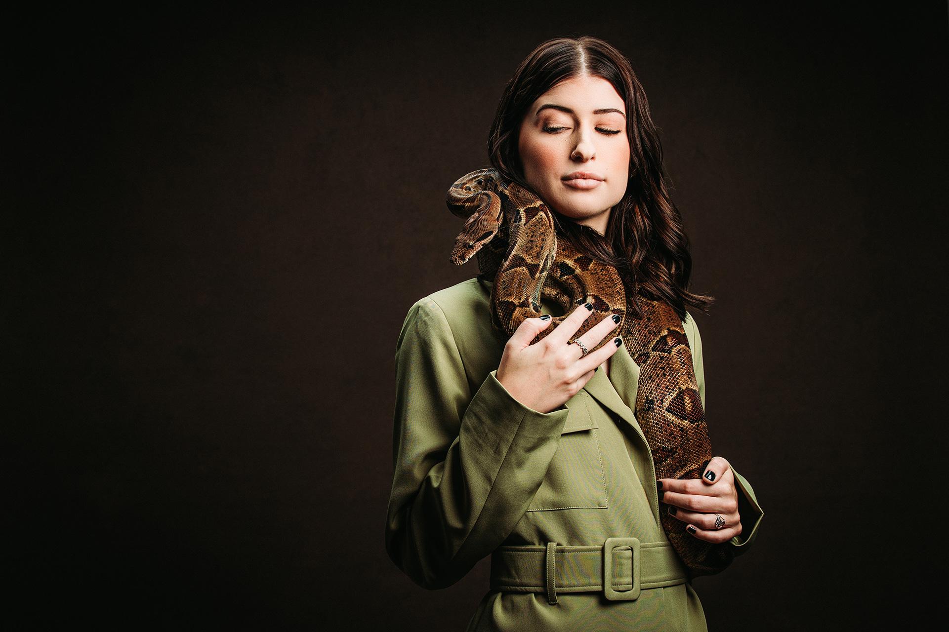 Senior photo of girl holding snake in studio.