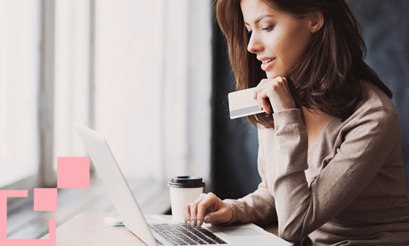 woman working on a laptop in front of a window holding a credit card