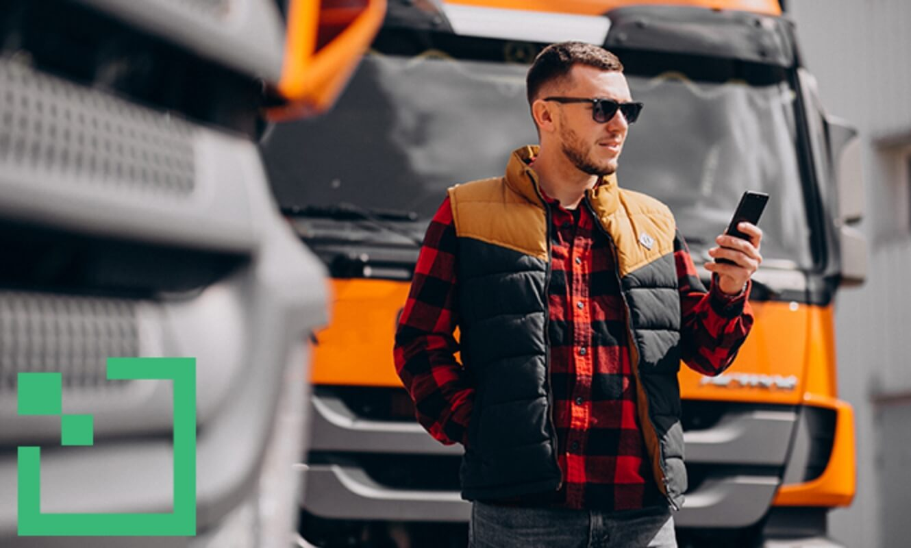 a man with sun glasses  holding a smart phone in front of a truck