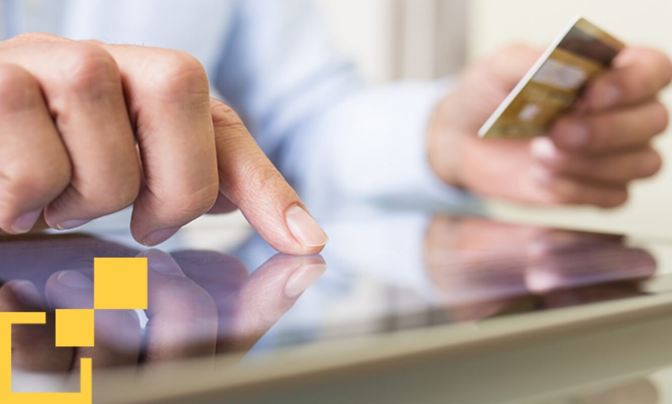 person pressing on a tablet holding a credit card