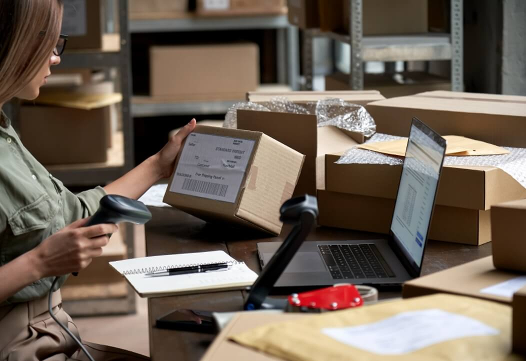 a woman surrounded by boxes scanning a parcel' label