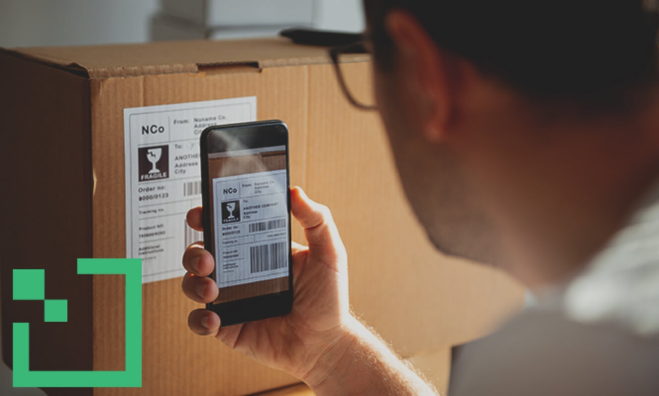 A man scanning a parcel's label with a smartphone