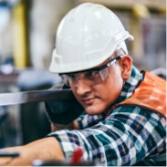 Person with protection helmet working on assembly line