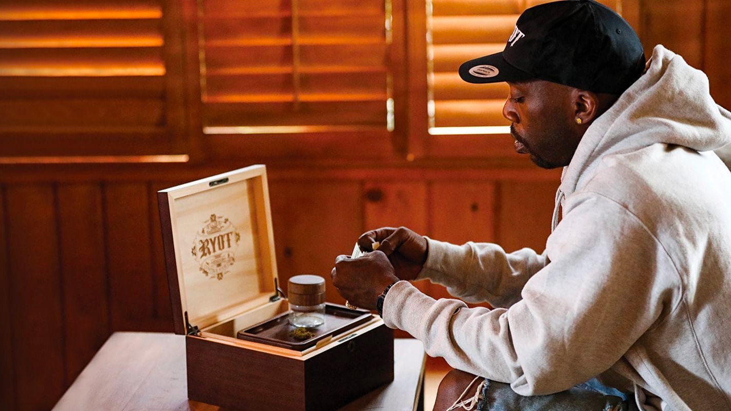 stylish man rolling a joint with a wooden tray and box from RYOT brand