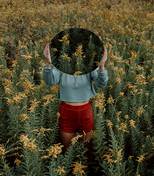 person in a flower field holding a mirror to the sky.