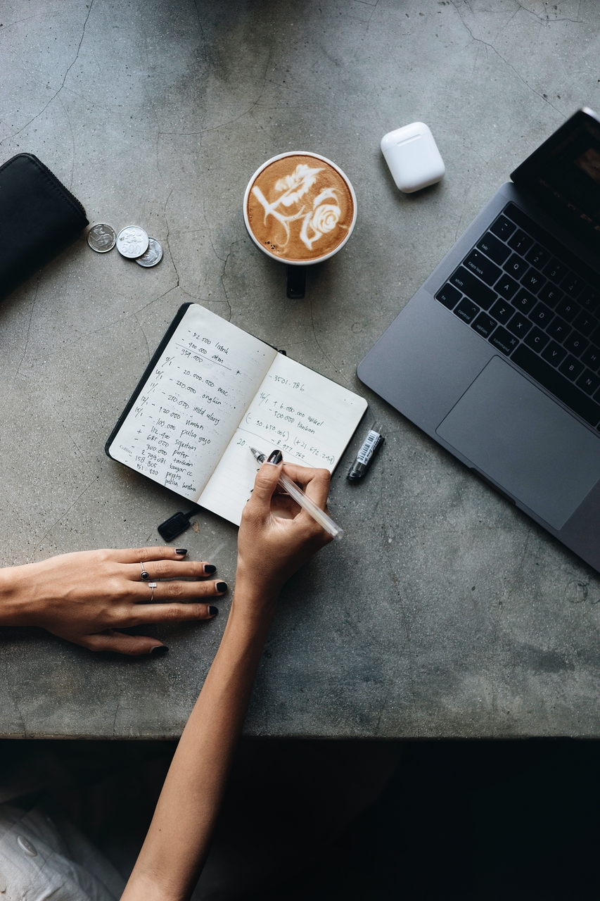 Top view of a person with a latte, writing in a notebook, and looking at a computer.