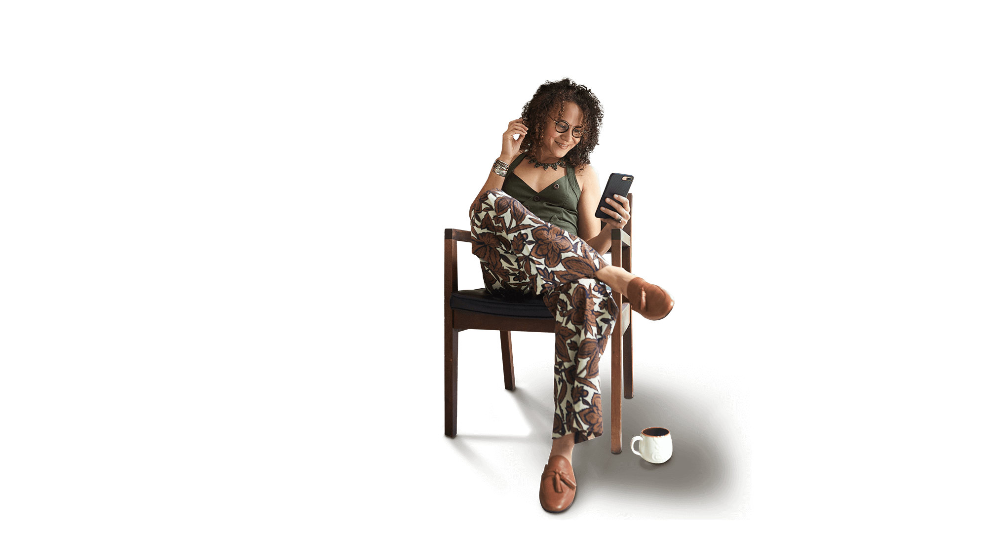 Mixed woman smiling at her phone drinking tea