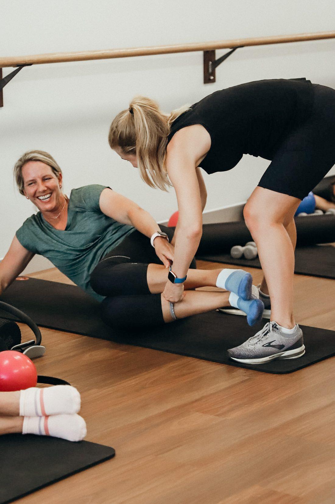 Pilates instructor teacher corrects student
