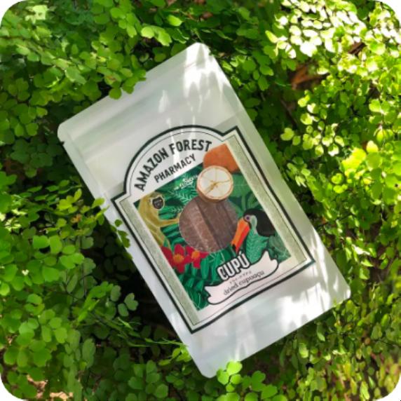 緑の植物の中に置かれたドライクプアスのパッケージ