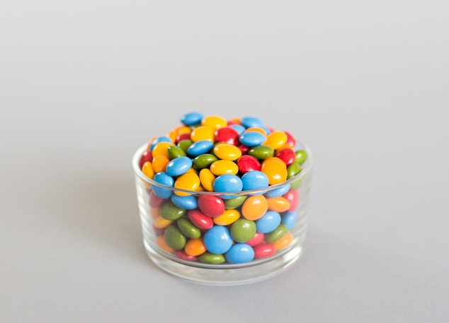 Colorful candy pills in bowl