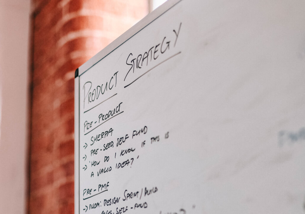 A white board with writing on it, the title being Product Strategy along with some additional product features and plans.