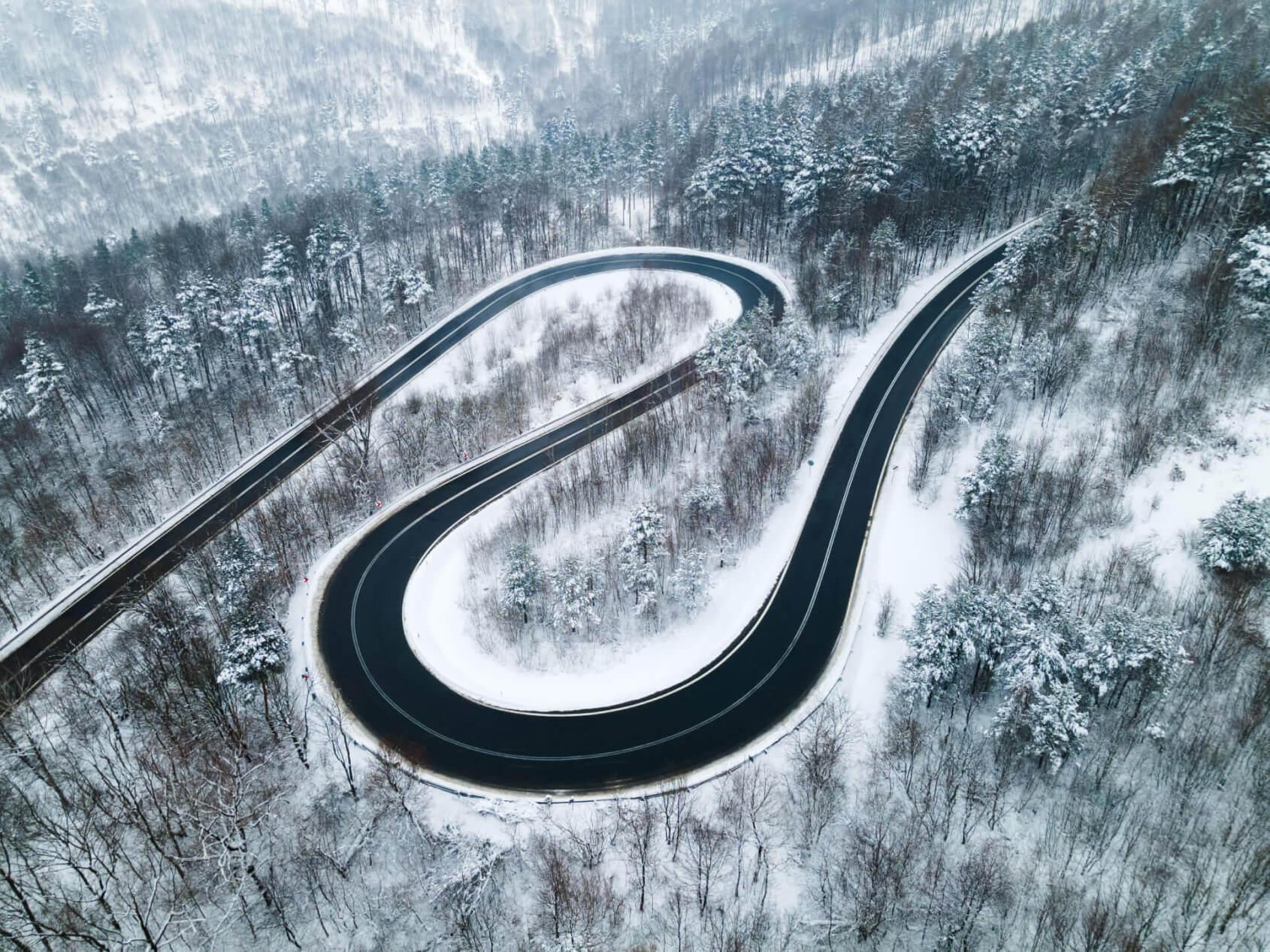 Gefährliche Kurven in verschneiter Berglandschaft gestreut mit Streusalzalternative