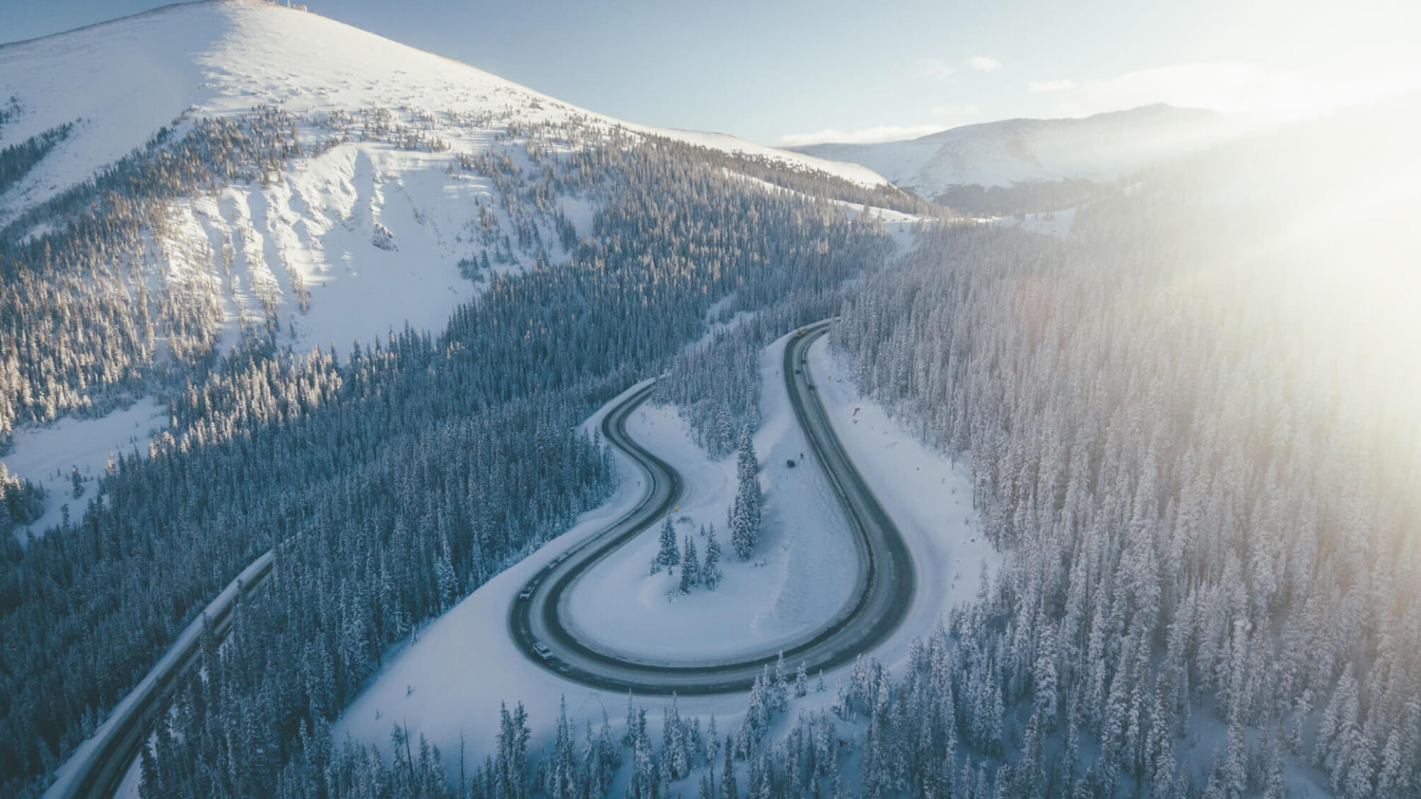 Kurvige Straße mit Streusalzalternative gestreut in verschneiten Bergen