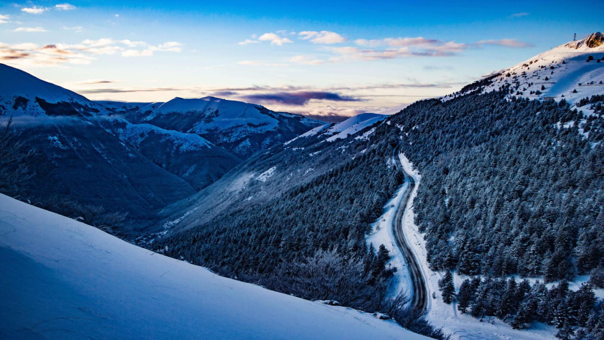 Schnee auf Bergen mit Wald und gestreuter Straße