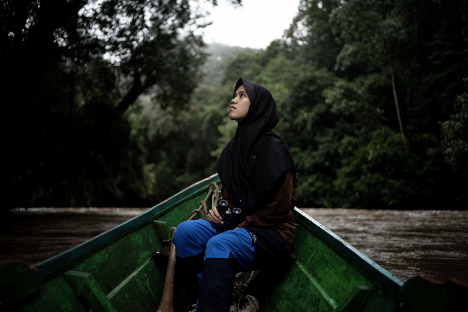 woman in Borneo on a canoe in the rainforest