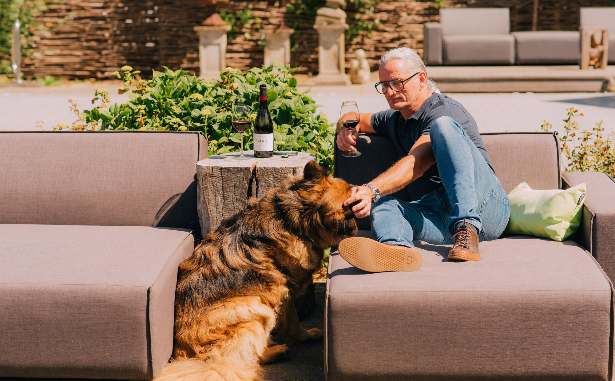 Bart op tuinmeubilair met hond