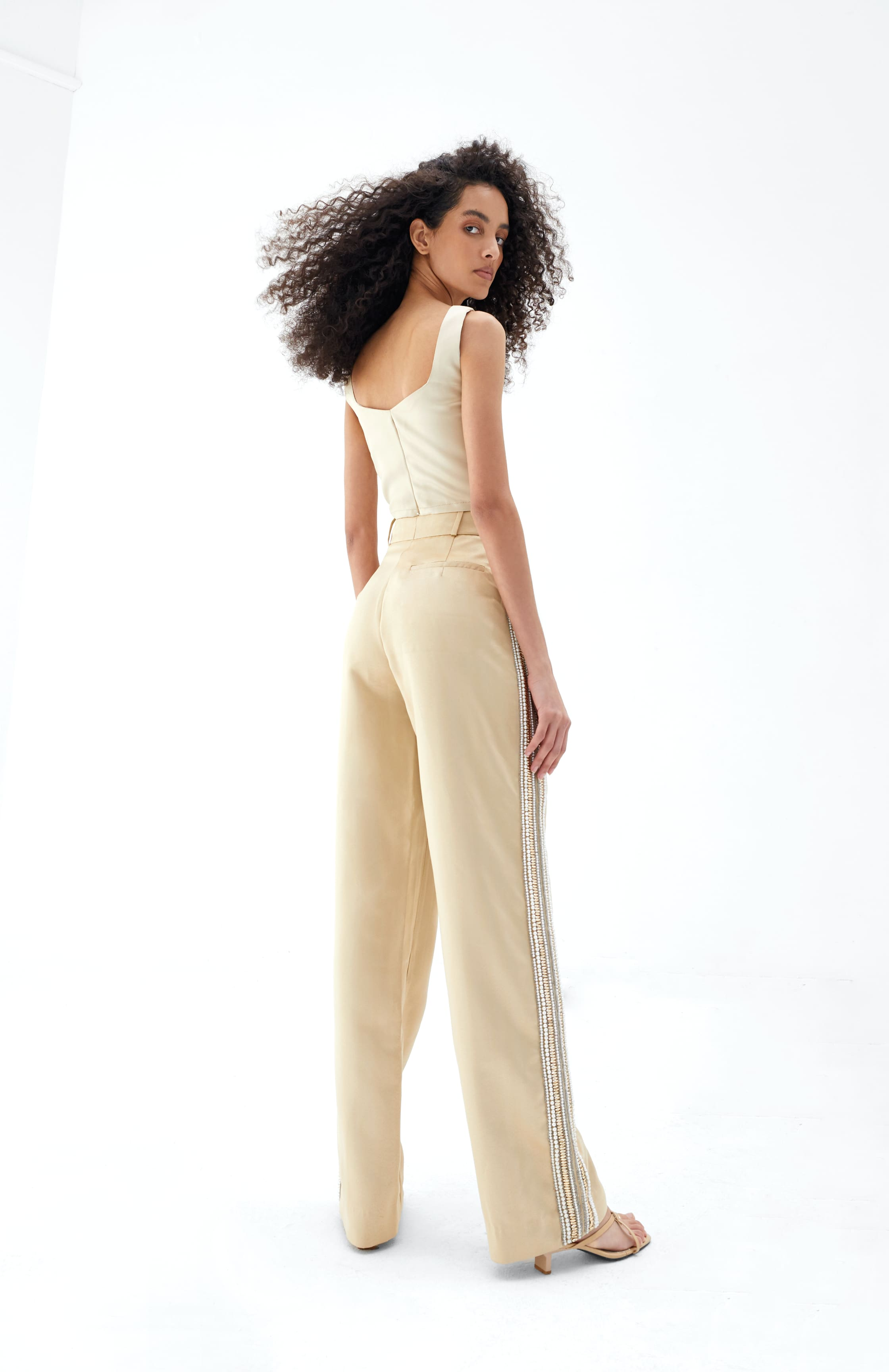 View 5 of model wearing Kismah Trousers in sand gold.