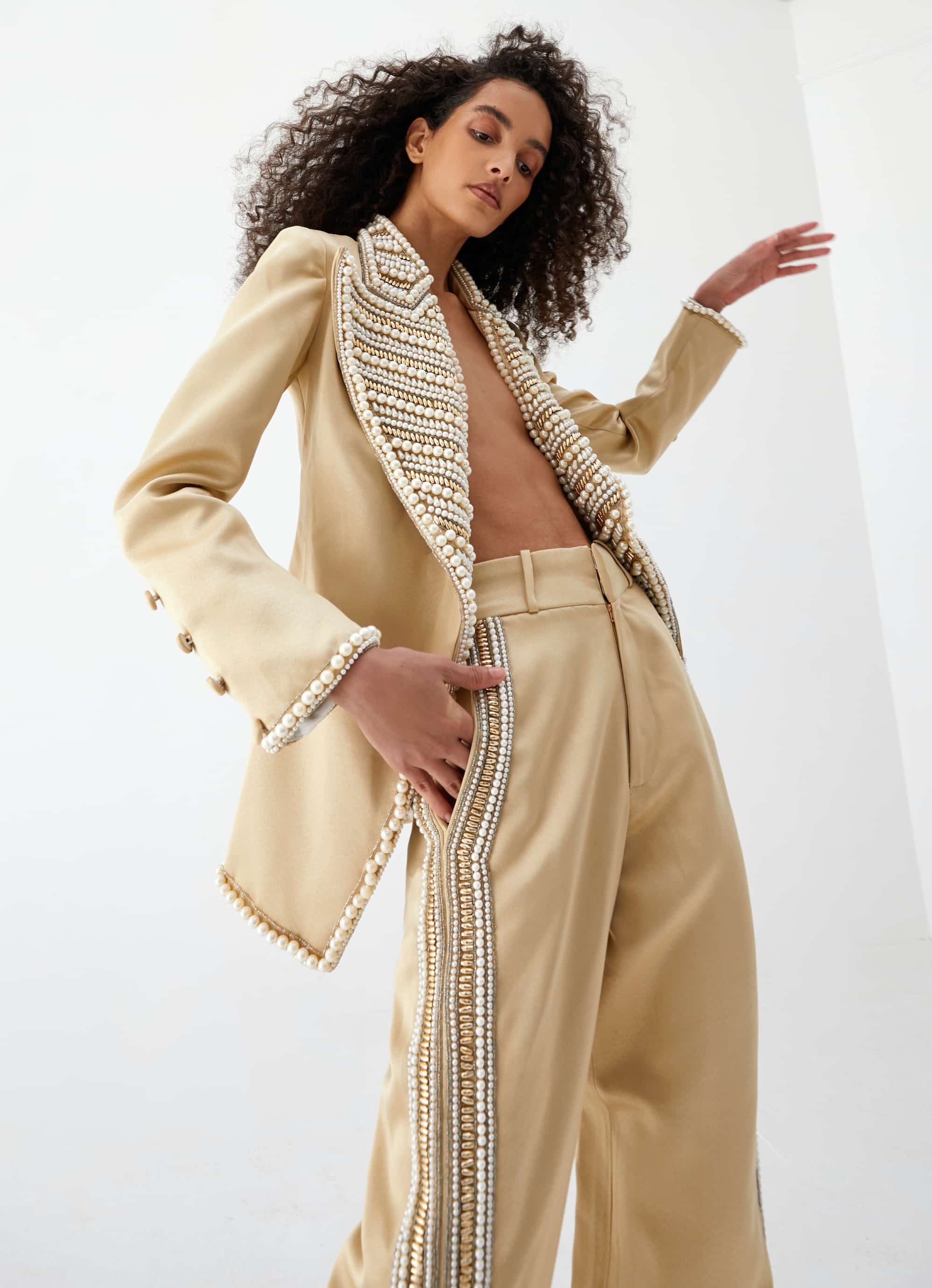 View 4 of model wearing Kismah Trousers in sand gold.