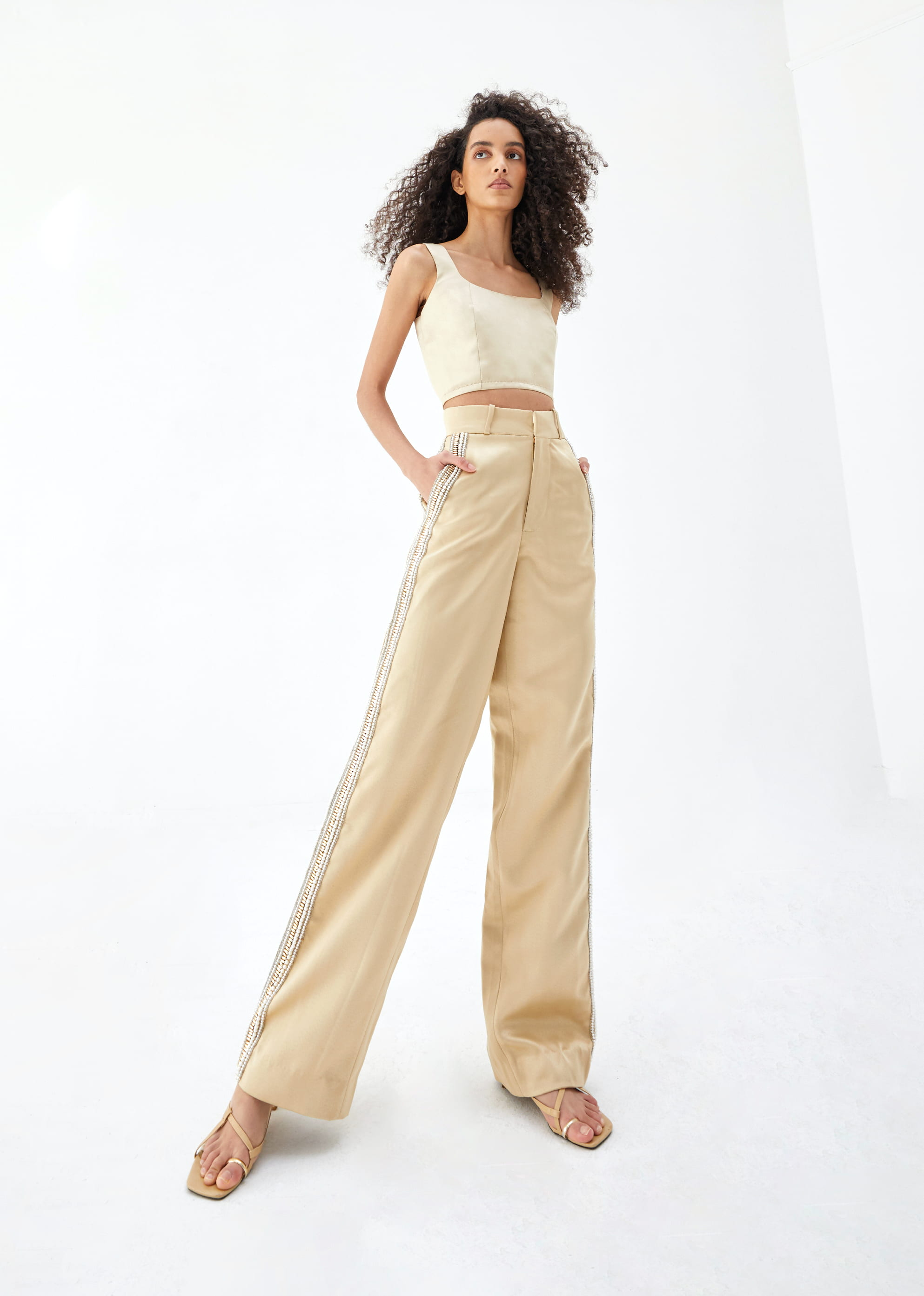 View 3 of model wearing Kismah Trousers in sand gold.
