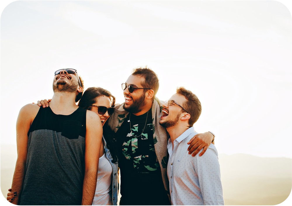 A group of four friends laughing and smiling.
