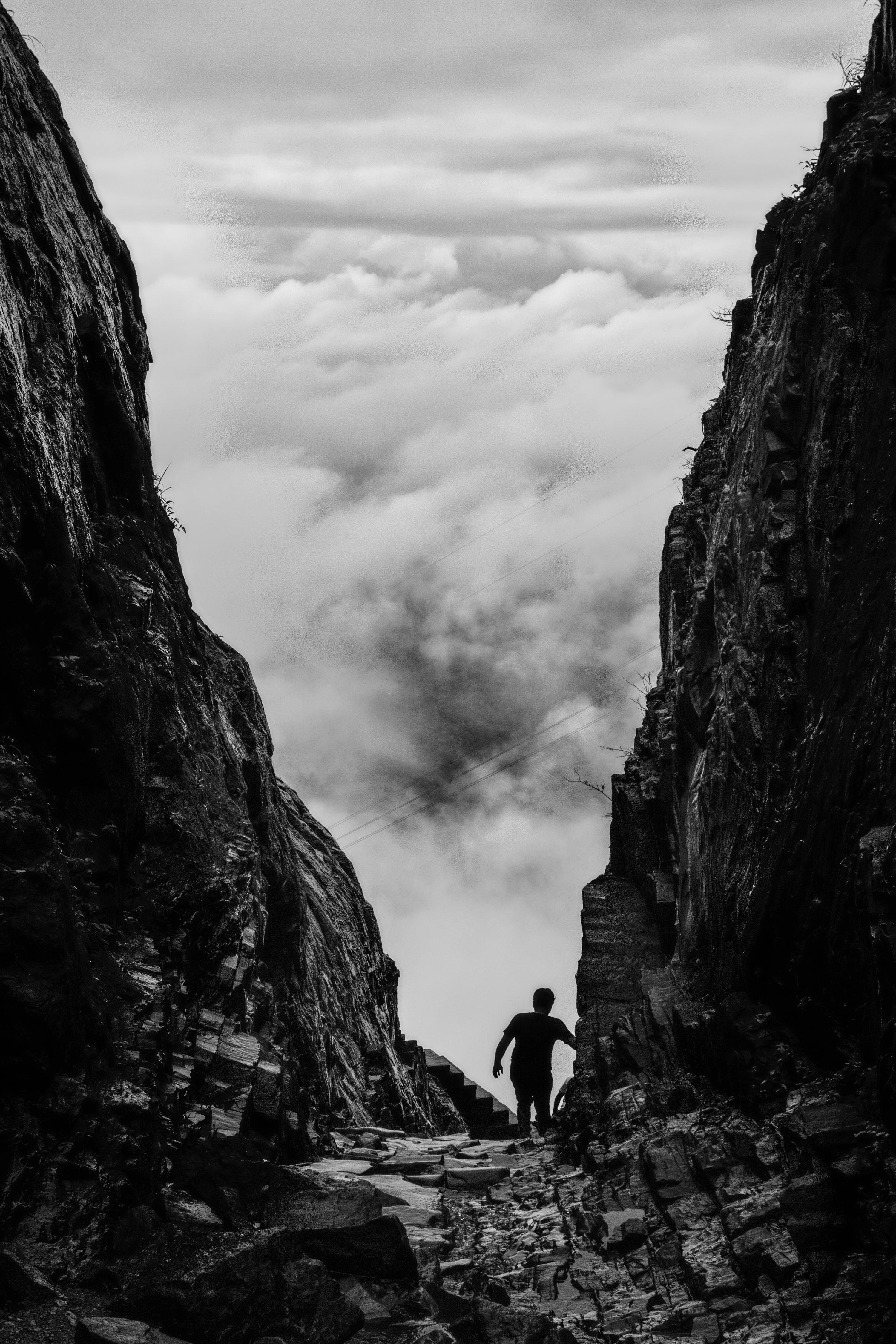 Black and white image of a ridge in between two cliffs.