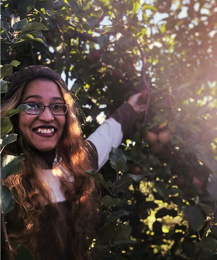 A picture of me smiling and picking an apple in a brown sweater and beanie