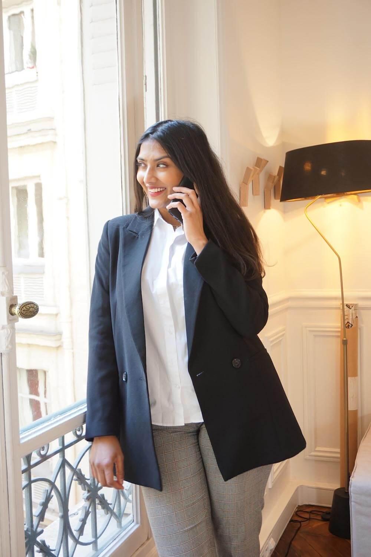 Mélanie au téléphone debout à la fenêtre