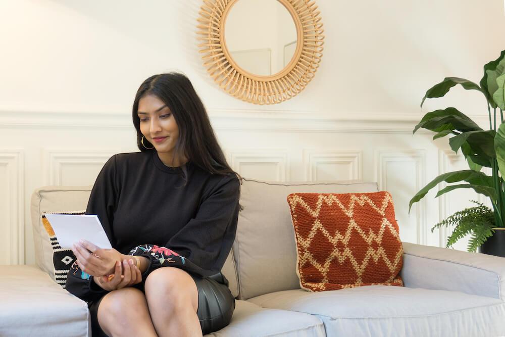 Mélanie lit ses notes assise sur un canapé